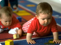 Two babies crawling on a carpet and playing with blocks.